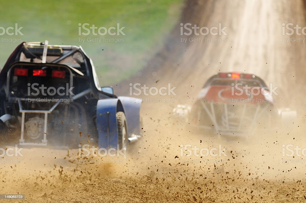 Two cars racing in a dirt road stock photo