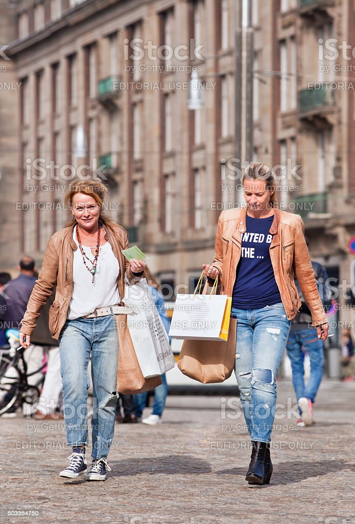 Two casual blond women with shoppjng bags on Dam Square stock photo