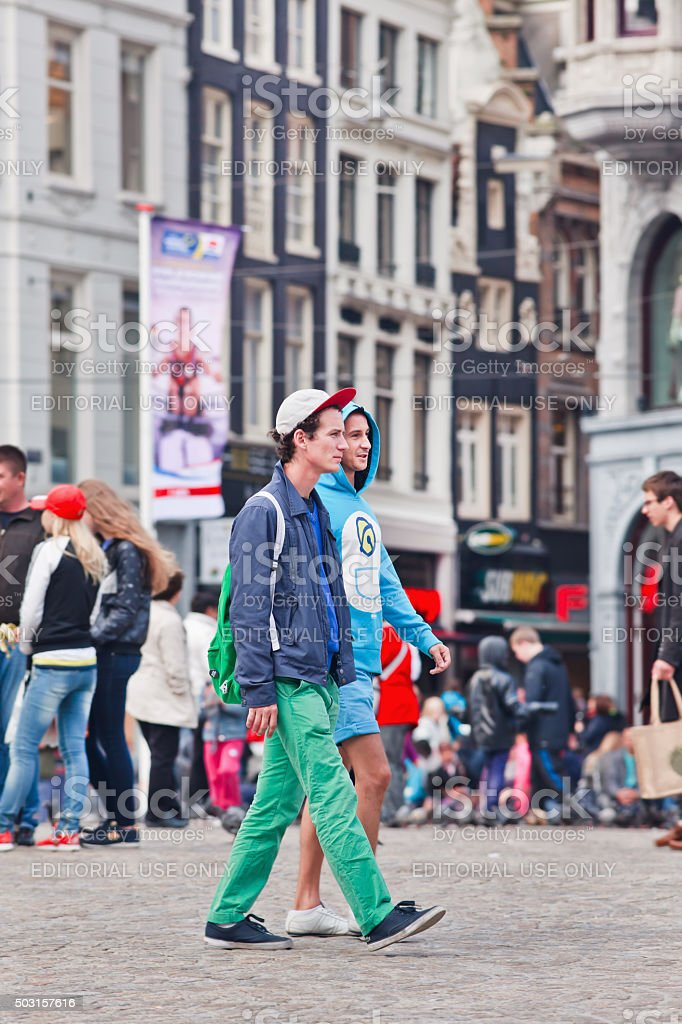 Two casual dressed young men walking on Amsterdam Dam Square stock photo