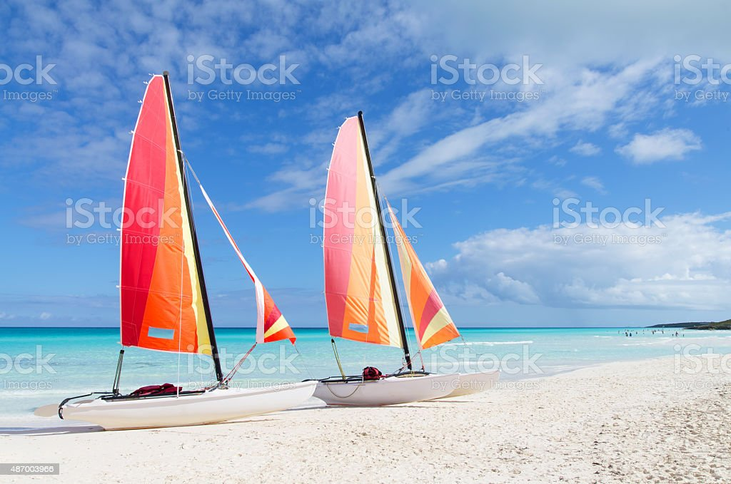 Two catamarans with its colorful sails wide open stock photo
