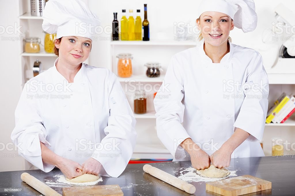 Two Caucasian Chefs/ Bakers Preparing Dough In A Professional Kitchen royalty-free stock photo