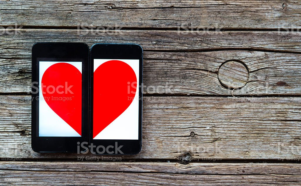 Two Cellphones With Half Heart Symbol stock photo
