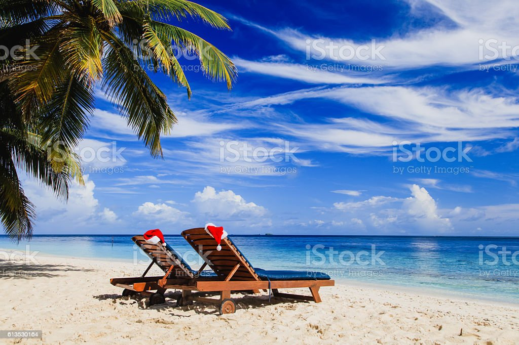 two chair lounges with red Santa hats on tropical beach stock photo