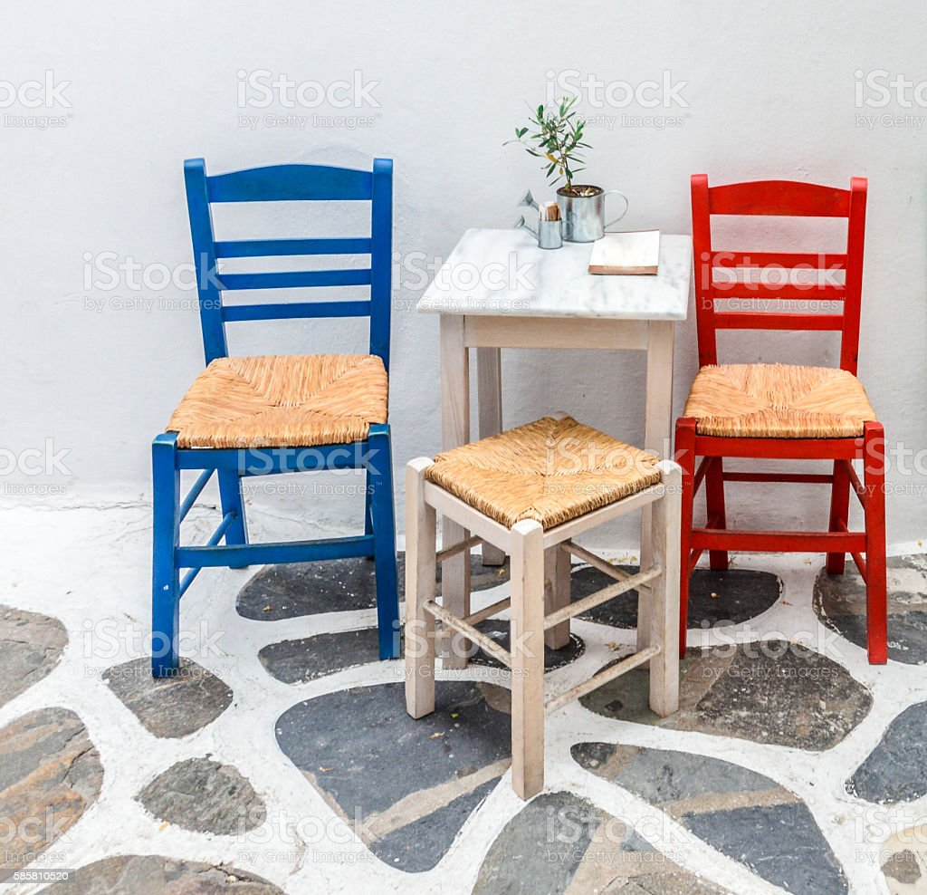Two chairs outside a Greek restaurant in traditional colors stock photo