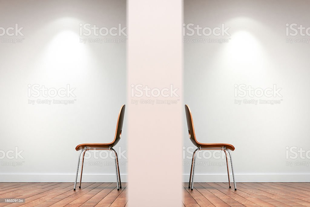 Two chairs split by wall stock photo