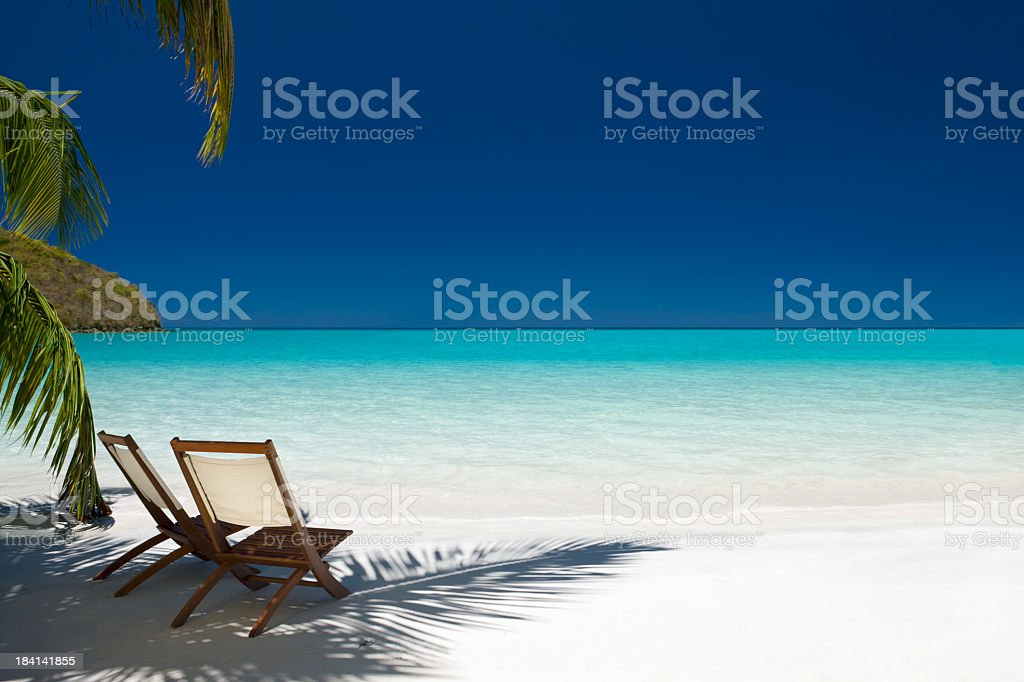 Two chairs under palm trees on Virgin Island beach stock photo
