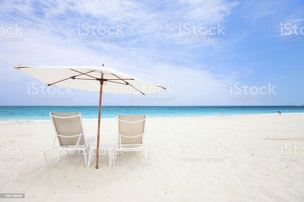 Two chairs under umbrella at beach stock photo
