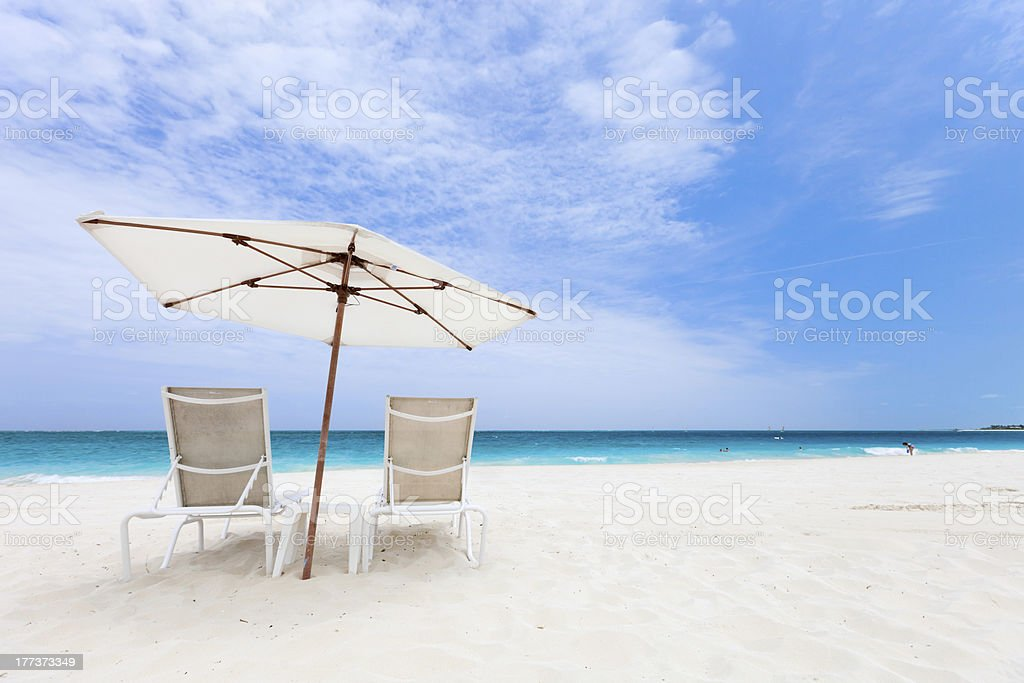 Two chairs under umbrella stock photo