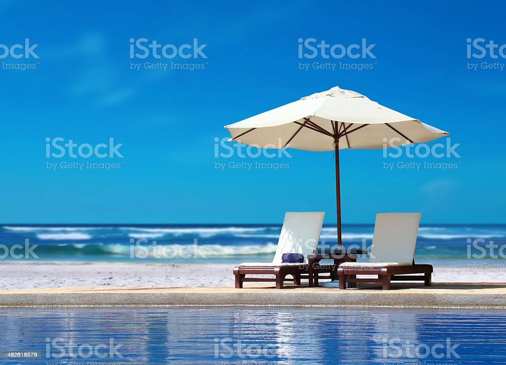 Two Chairs with White Umbrella near the Beach stock photo