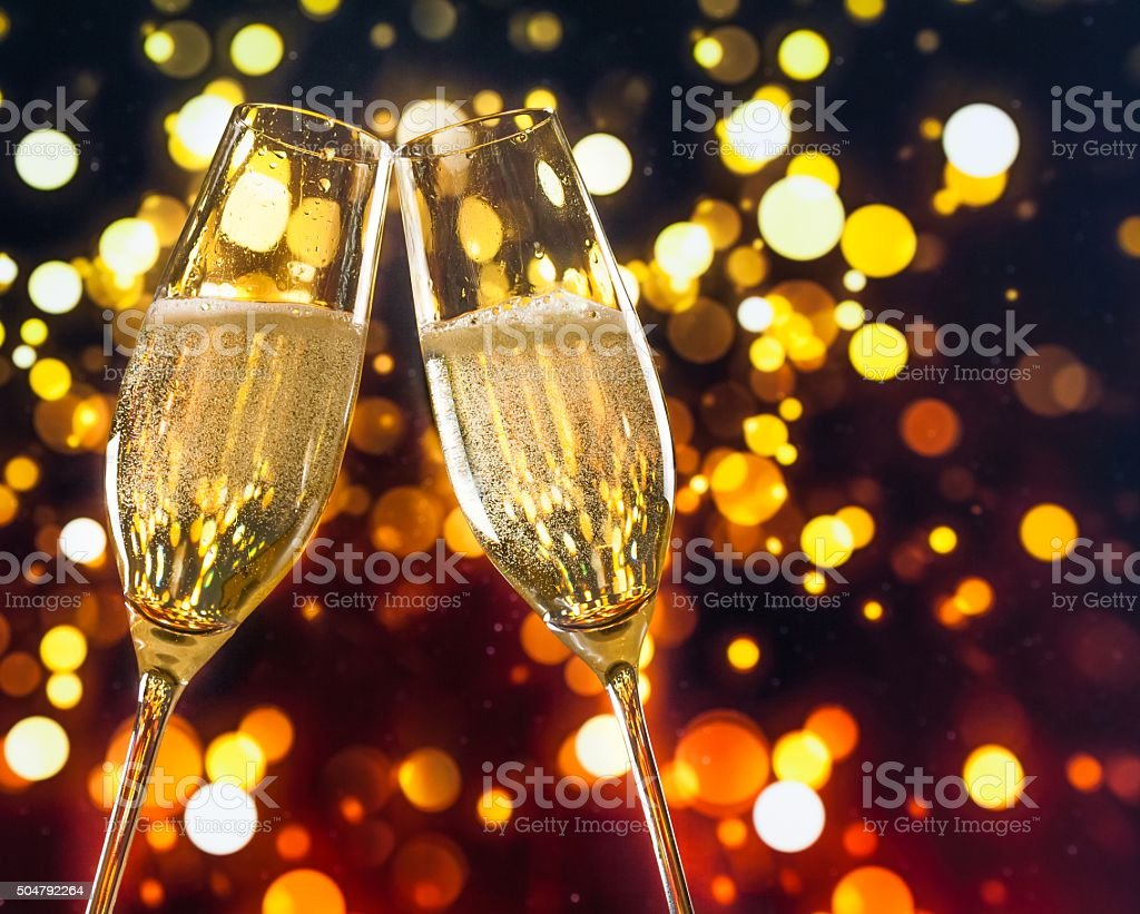 two champagne flutes with golden bubbles make cheers stock photo