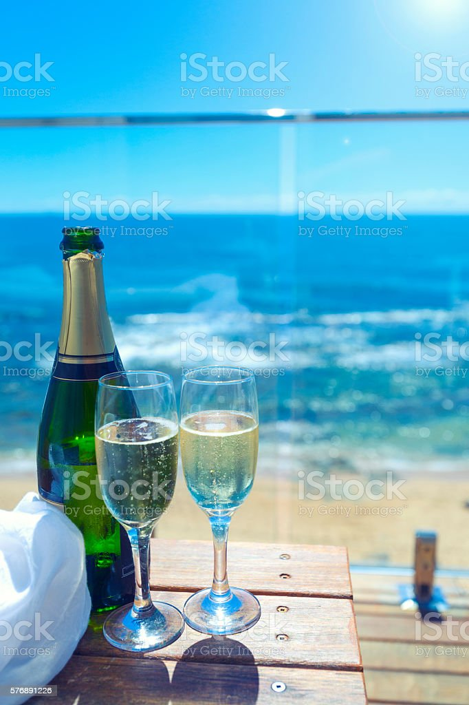 Two champagne glasses and bottle at the sea side. stock photo