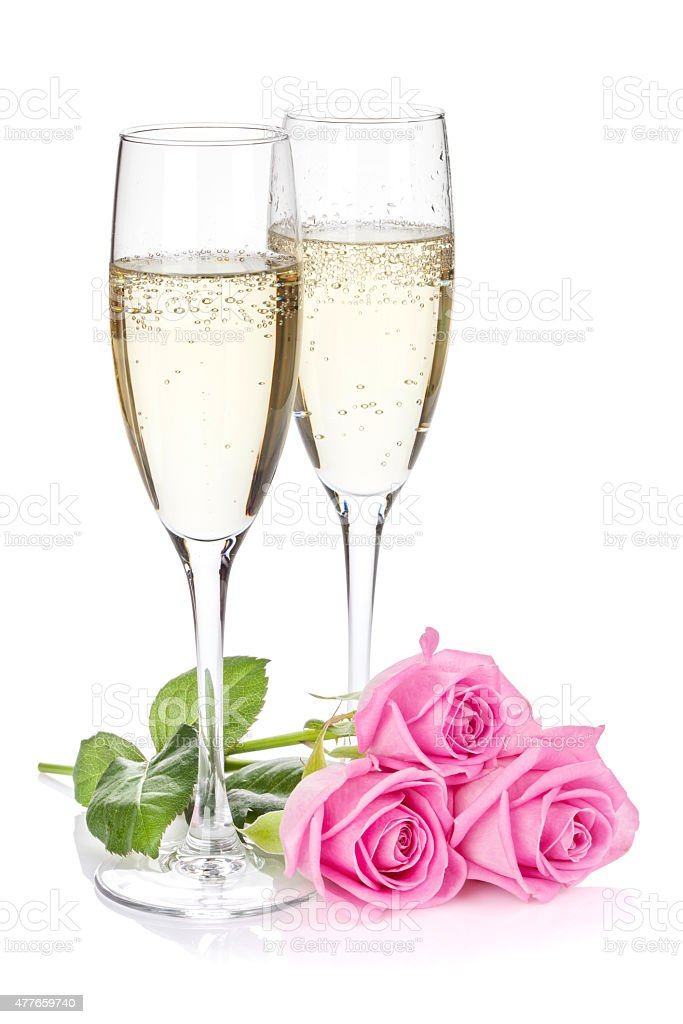 Two champagne glasses and pink rose flowers stock photo