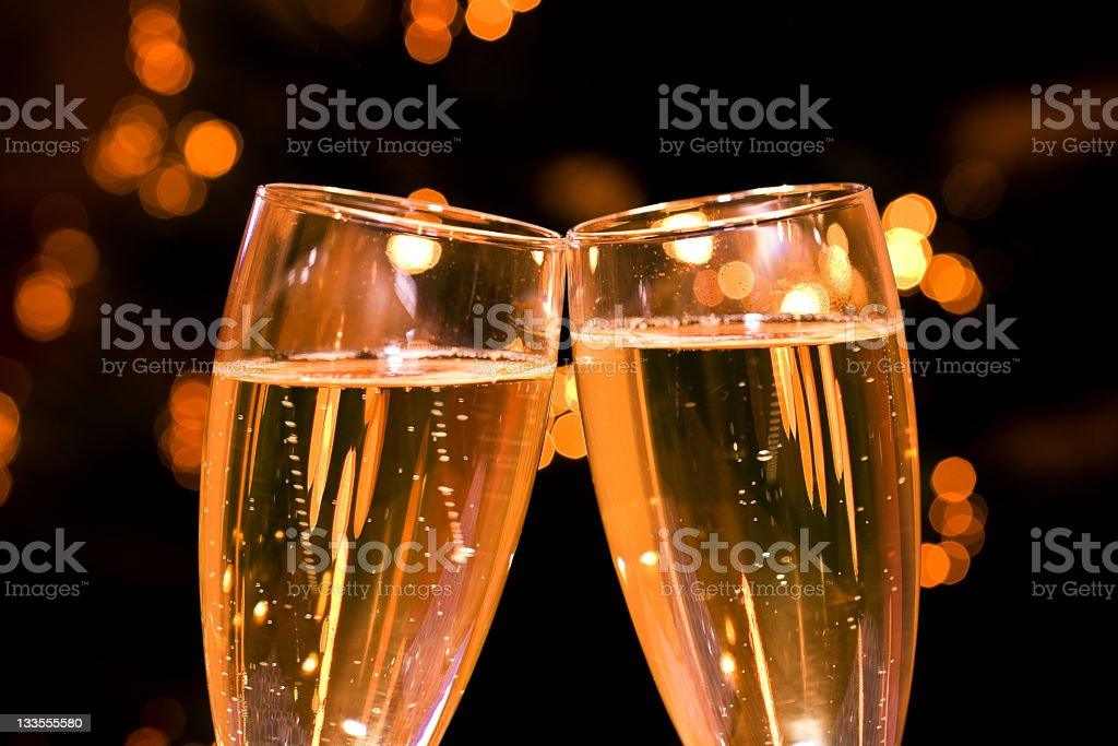 Two champagne glasses toast together over bokeh background royalty-free stock photo