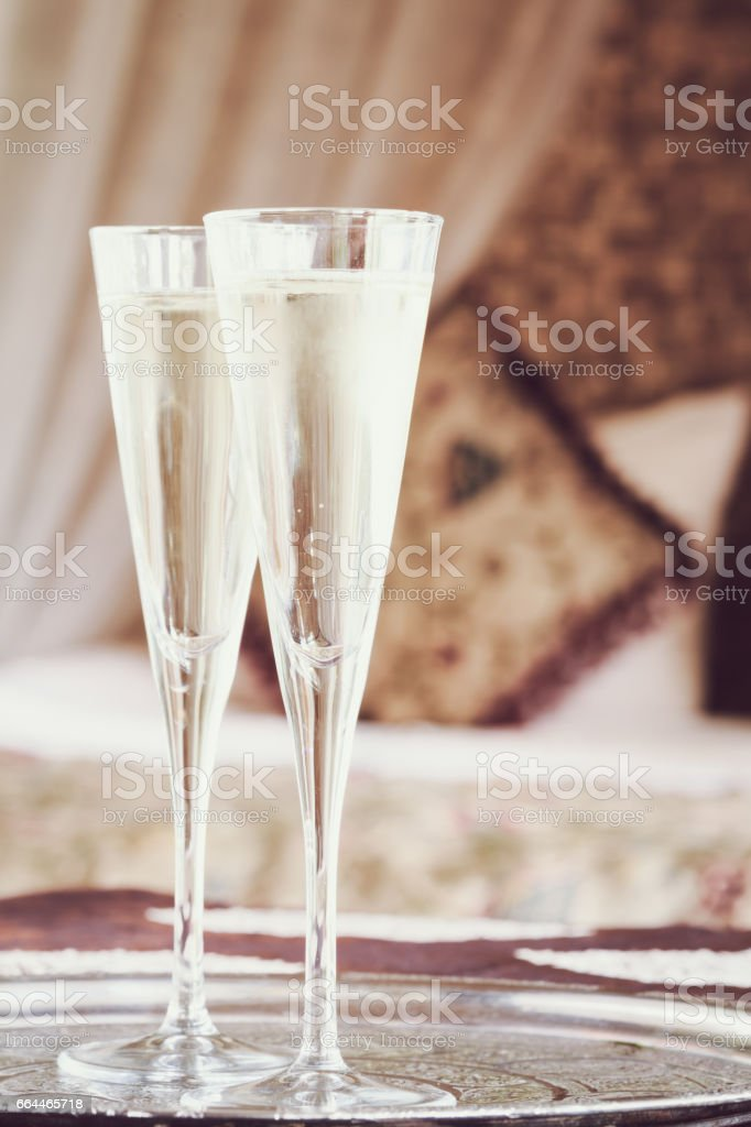 Two champagne glasses with oriental canopy bed at the background stock photo