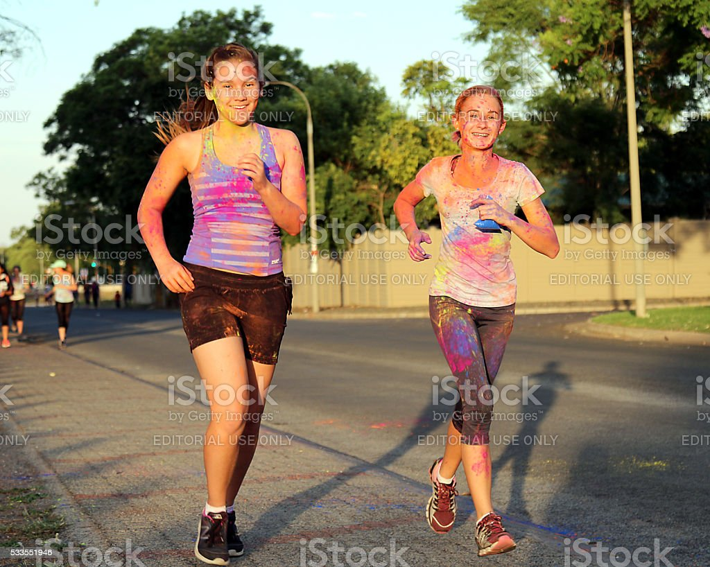 Two Chearful running teen girls covered with powder paint stock photo