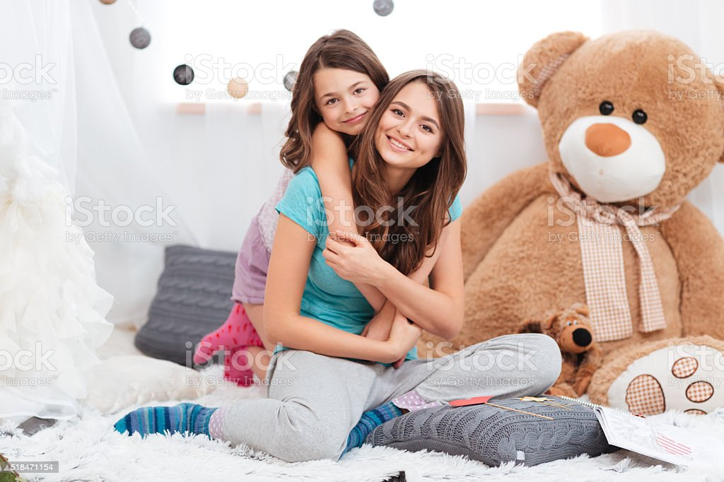Two cheerful charming sisters sitting in children room stock photo