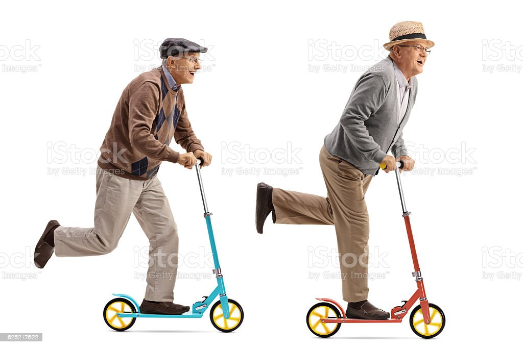 Two cheerful elderly men riding scooters stock photo