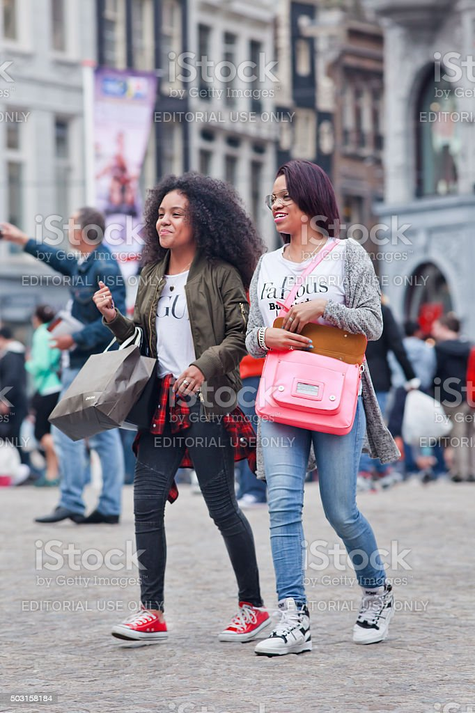 Two cheerful exotic girls walking on Amsterdam Dam Square stock photo