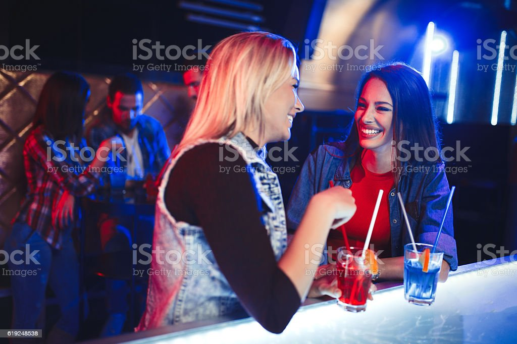 Two cheerful female friends having fun in night club stock photo