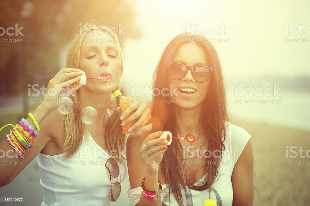 Two cheerful friends having fun and blowing bubbles stock photo