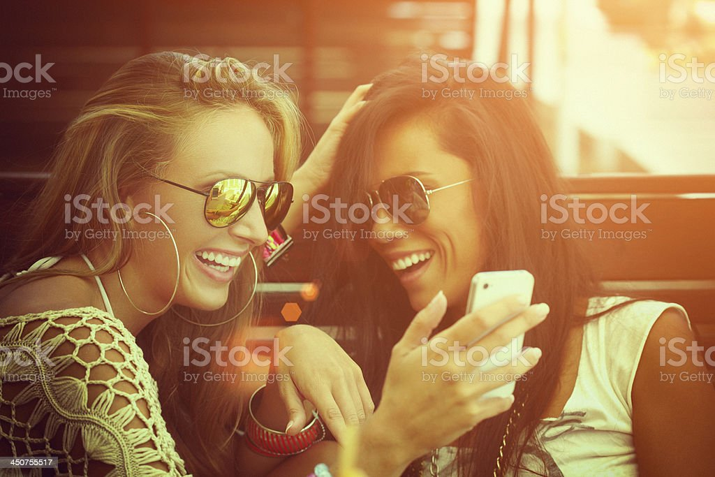Two cheerful friends having fun and looking at mobile phone stock photo