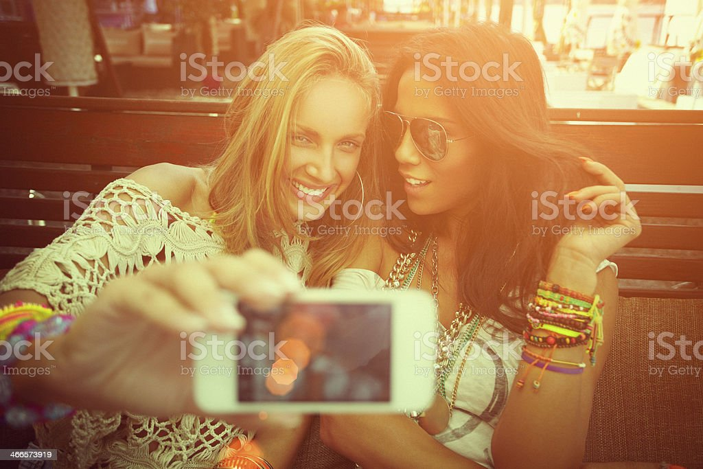 Two cheerful friends taking photos of themselves on smart phone stock photo