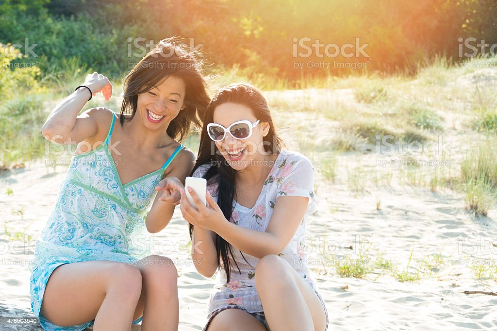 Two cheerful friends using  smart phone on the beach stock photo