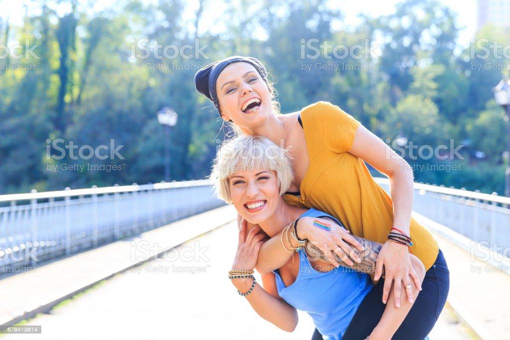 Two cheerful girls embracing and having fun on bridge stock photo