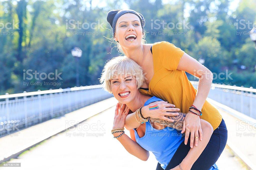 Two cheerful girls having fun in piggyback ride on bridge stock photo