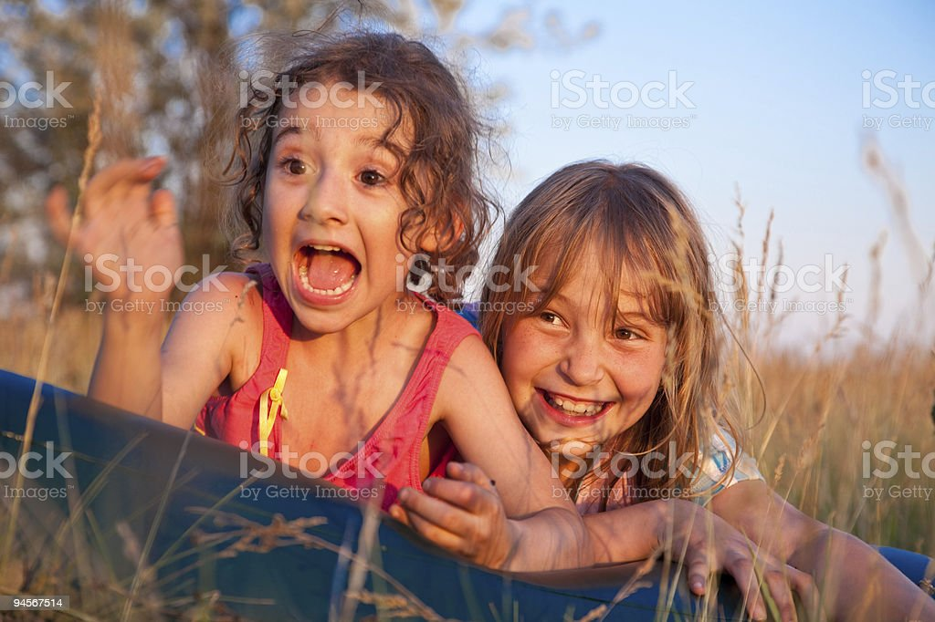 Two cheerful girls lie in grass royalty-free stock photo