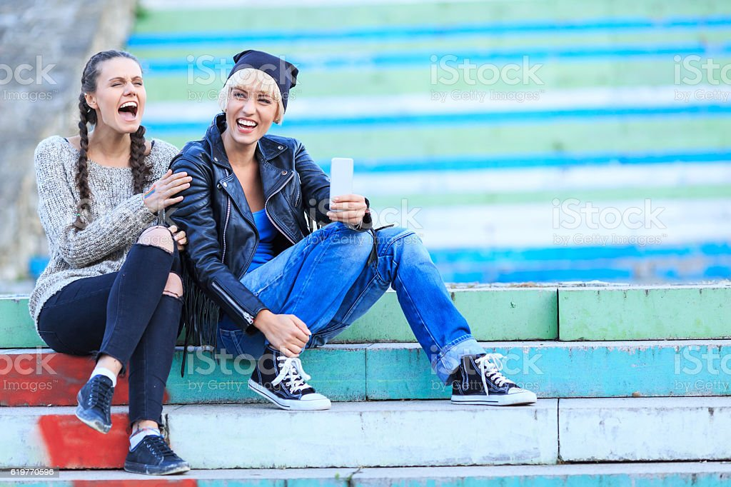 Two cheerful girls sitting on stairs stock photo