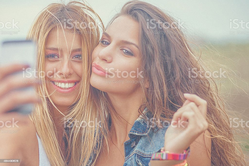 Two cheerful hipster friends taking selfie photos on smart phone stock photo