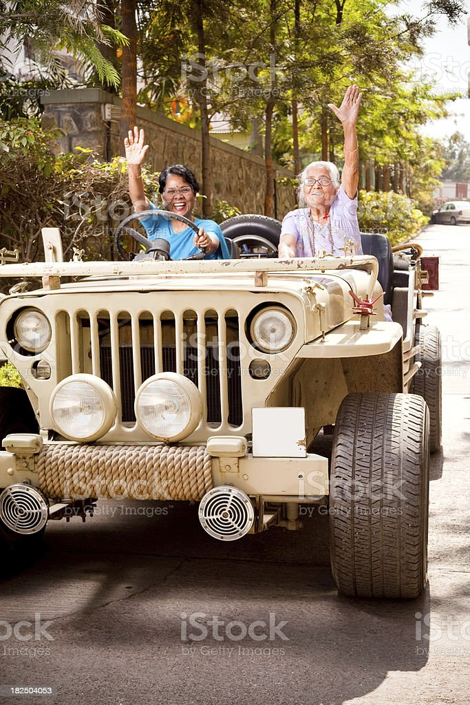 Two Cheerful Indian Female Senior Mother and Daughter with Jeep stock photo