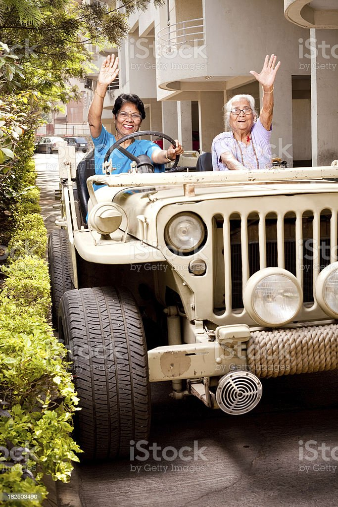 Two Cheerful Indian Senior Mother and Daughter with Jeep stock photo