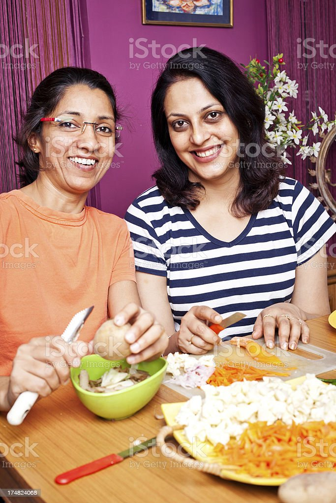 Two Cheerful Indian Women Preparing food cutting vegetables royalty-free stock photo