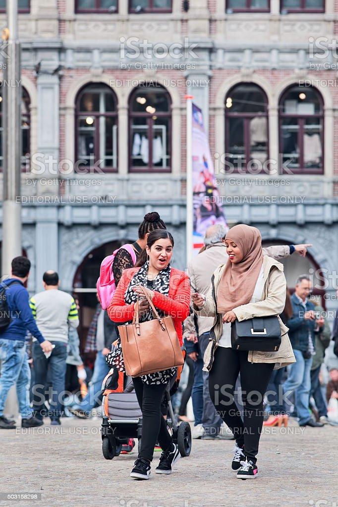 Two cheerful Muslim girls walking on the Amsterdam Dam Square stock photo