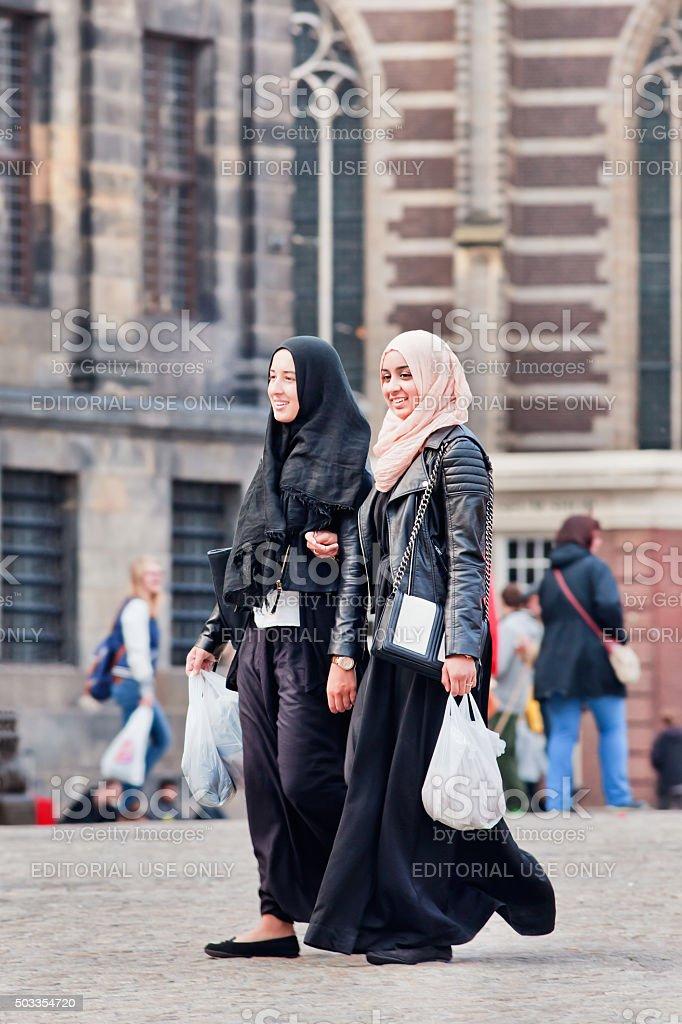 Two cheerful Muslim girls with headscarf walk on Dam Square stock photo