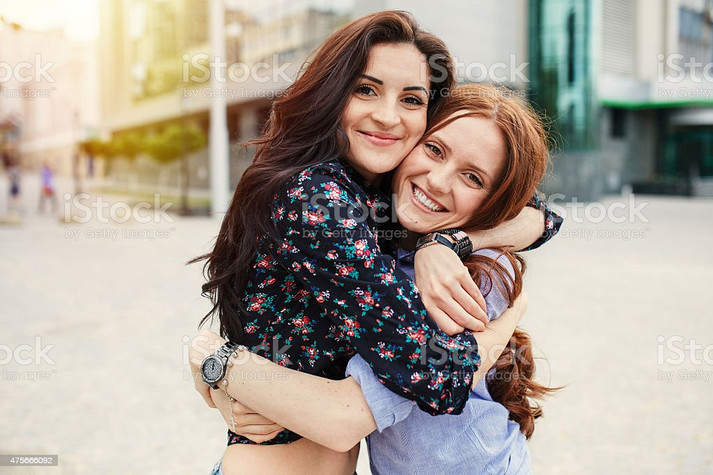 Two cheerful sisters hugging stock photo