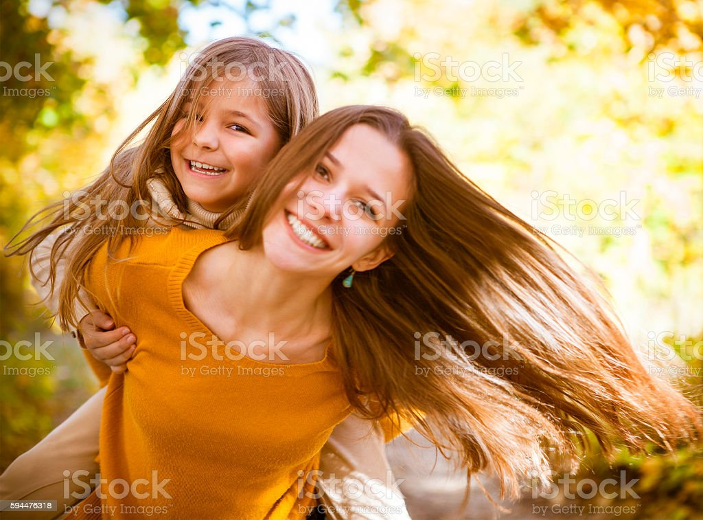 Two cheerful sisters playing in the park stock photo