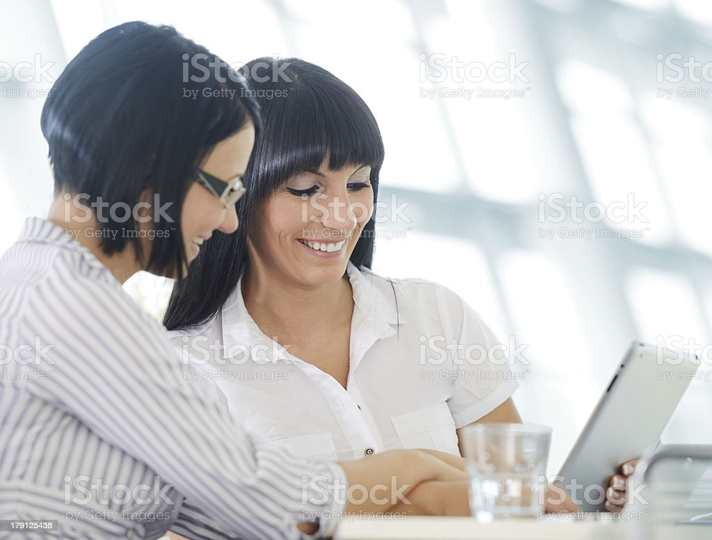 Two cheerful smiling young business women working at office royalty-free stock photo