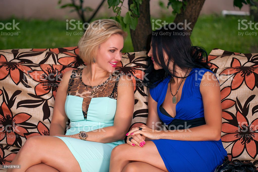 Two cheerful woman sitting on the couch outdoors stock photo