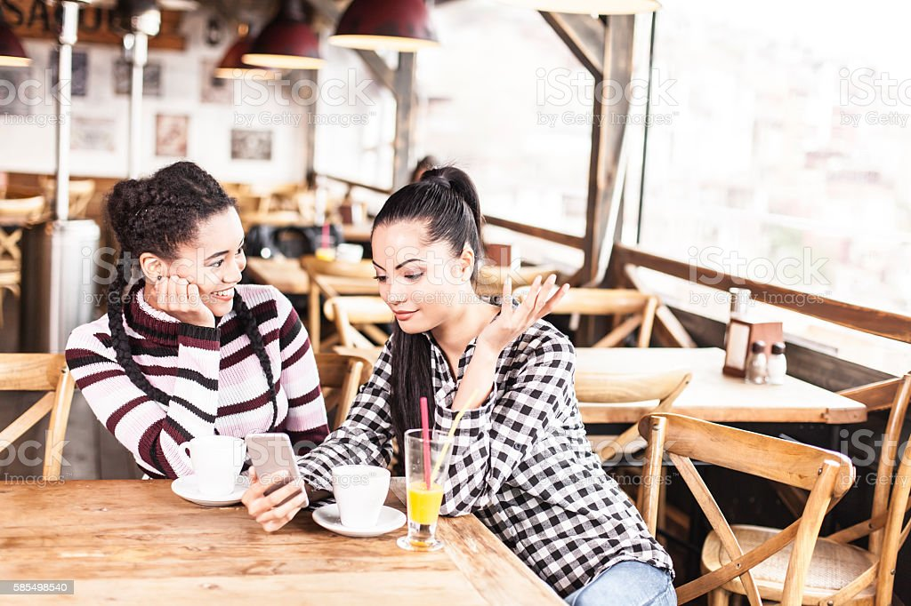 Two cheerful young women using smart phone at coffee shop stock photo