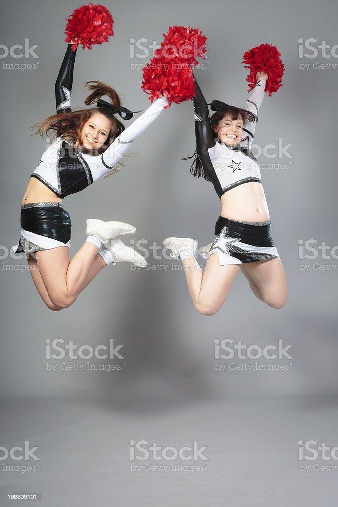two cheerleaders jumping stock photo