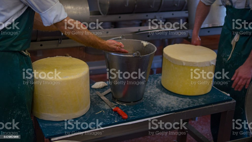 Two cheese makers cleaning stock photo