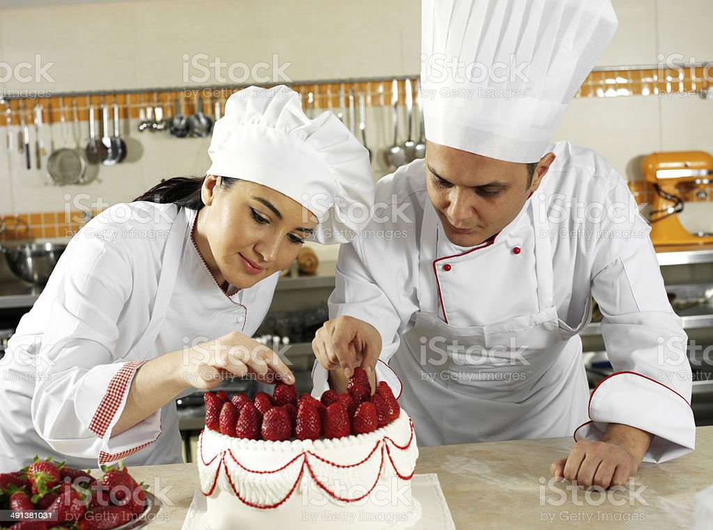 Two Chef Decorating Cake stock photo