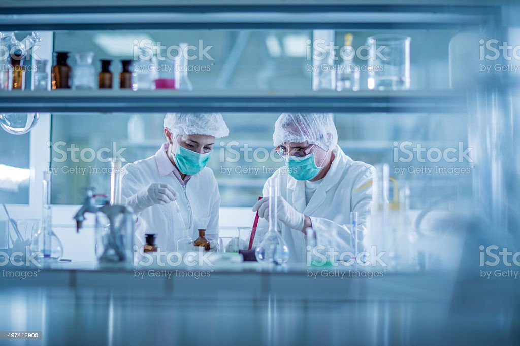 Two chemists examining chemicals for their scientific research in laboratory. stock photo