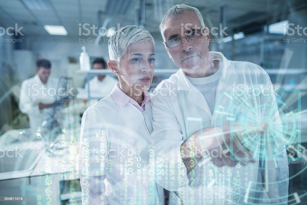 Two chemists working on digitally generated image on touch screen. stock photo
