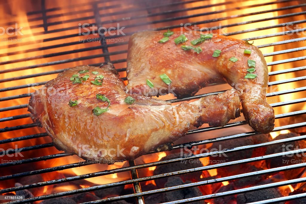 Two Chicken Quarter On The Hot BBQ Grill Close-up. stock photo