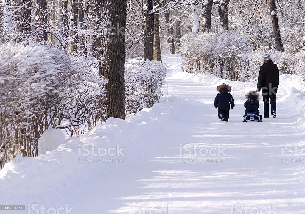 Two children and an adult all bundled up for a winter walk royalty-free stock photo