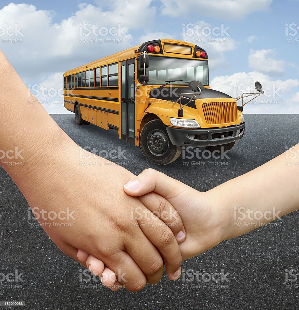 Two children are holding hands waiting for the school bus royalty-free stock photo